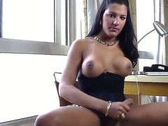 Sexy and arousing dark haired sexy shemale Stefane Marinho with big breasts and hard rod enjoys in posing and playing with her cock for the camera in a hotel room on the chair.
